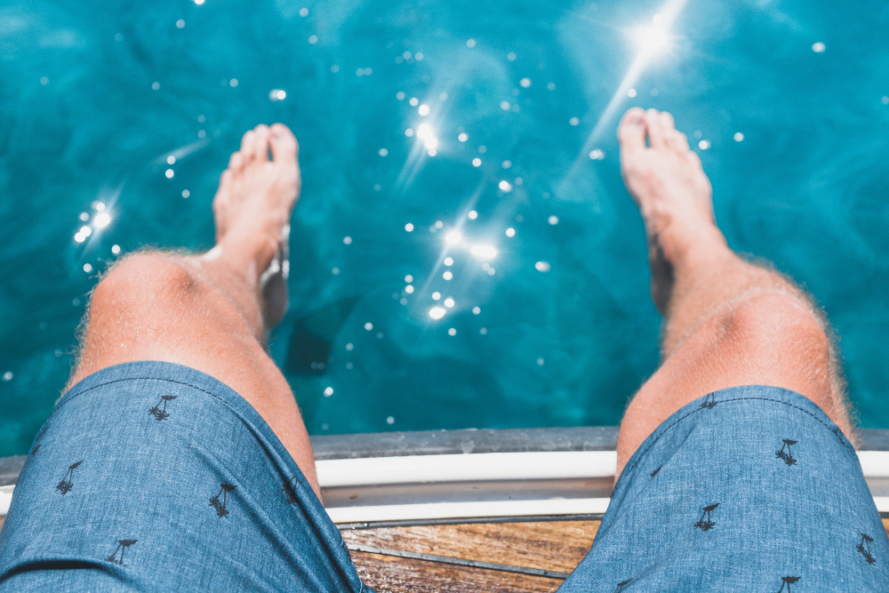 young man's knees next to sparkling swimming pool